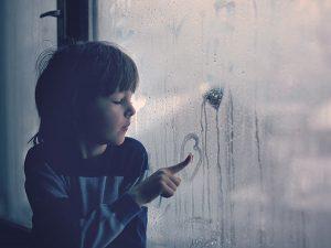 Child drawing on window humidity