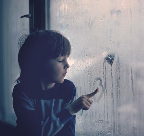 Child drawing on window humidity